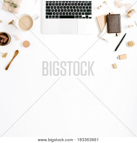 Blogger or freelancer workspace with laptop coffee mug notebook sweets and accessories on white background. Flat lay top view minimalistic brown styled home office desk. Beauty blog concept.