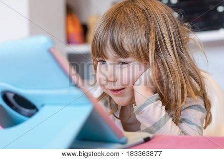 Smiling Little Child Watching Digital Tablet