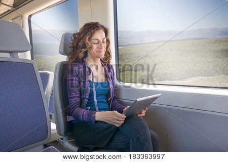 Smiling Woman In Train Reading Digital Tablet