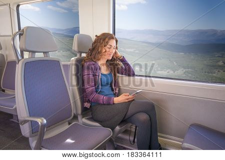 Smiling Woman Sitting In Train Using Mobile