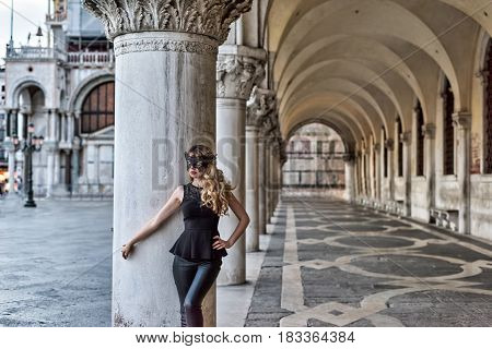 Blonde Girl wearing a black mask in San Marco Square, Italy