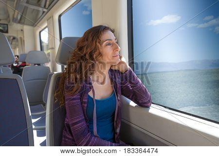 Woman Sitting In Train Looking Through The Window