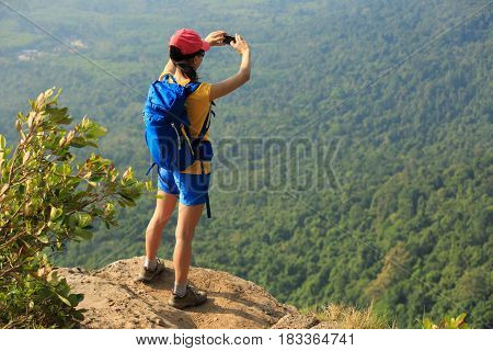 successful woman hiker taking photo with smartphone on mountain peak cliff