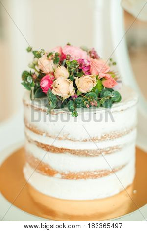 Decorated white naked cake rustic style for weddings birthdays and a events.