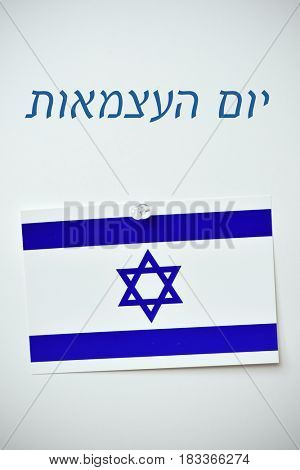 the text Yom Haatzmaut, Independence Day written in Hebrew, and an Israeli flag pinned with a push-pin to an off-white background
