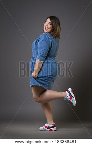 Plus size fashion model in casual clothes fat woman on gray studio background overweight female body full length portrait