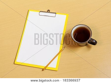 Clipboard with white sheet cup of tea and pencil on desk