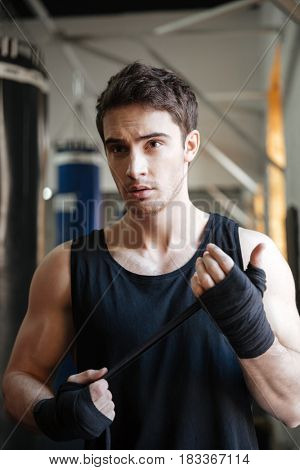 Strong serious sportsman looking away agressively while training in gym