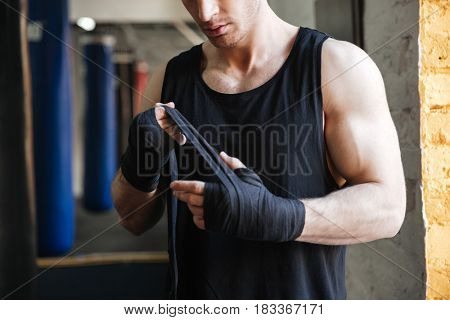 Cropped image of strong man wearing black gloves for boxing in gym