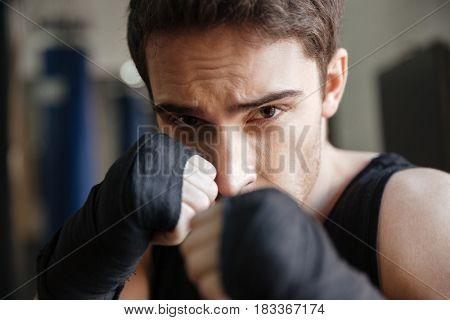 Close up  view of a serious boxer doing exercise in gym and looking at the camera