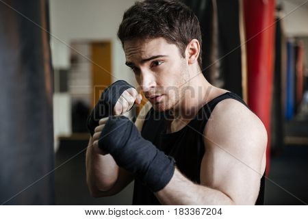 Close up view of a boxer training in gym with punchbag