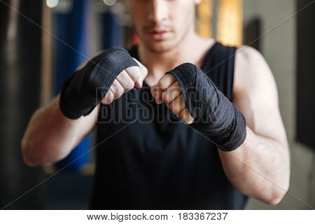 Cropped image of boxer standing in gym. Focus on hands