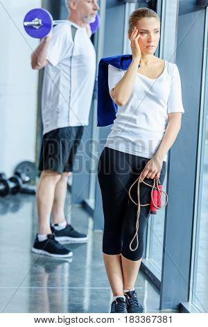 Sportswoman Having Headache And Holding Skipping Rope, Sportsman Holding Barbell Behind
