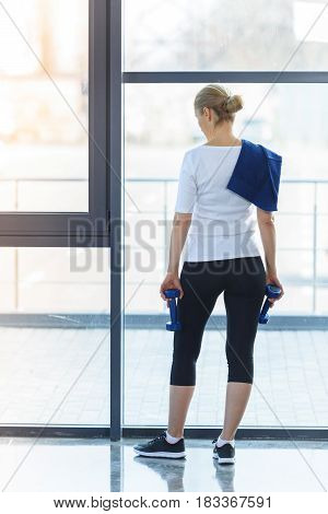 Back View Of Blonde Woman Standing And Holding Dumbbells In Gym