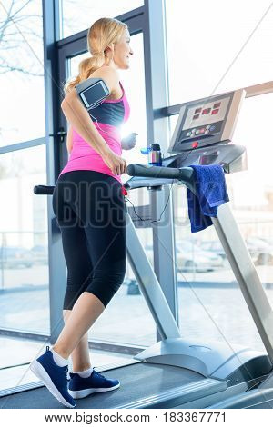 Low Angle View Of Sporty Blonde Woman Training On Treadmill In Gym