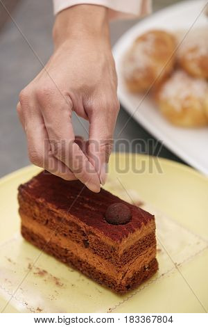 Hand of the woman confectioner preparing chocolate cake