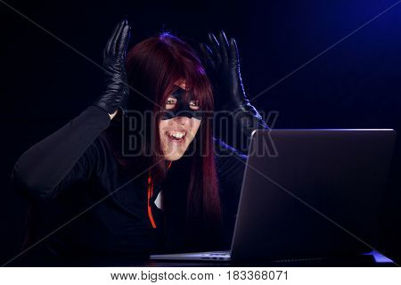 Surprised night hacker by laptop