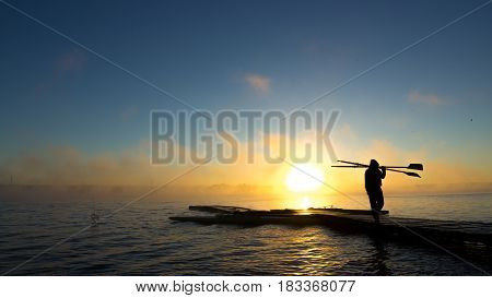 Rower silhouette with a fog in the background at the sunrise in Brasilia
