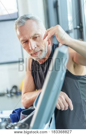 Sporty Bearded Mature Man Leaning At Equipment In Gym