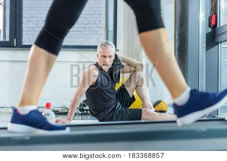 Bearded Mature Sportsman Sitting On Yoga Mat With Towel While Woman Training On Treadmill