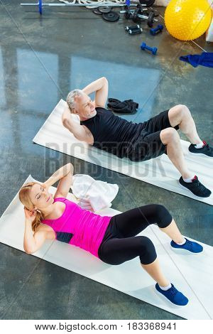 High Angle View Of Smiling Man And Woman In Sportswear Doing Abs In Gym