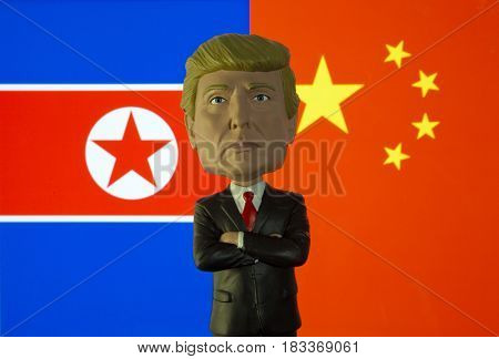 Bobble head caricature of United States President Donald Trump standing in front of the flag of North Korea and China