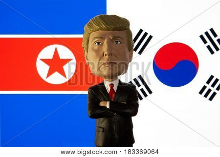 Bobble head caricature of United States President Donald Trump standing in front of the flag of North Korea and South Korea.