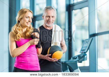 Smiling Mature Sportsman And Sportswoman With Towels And Ball Standing Together In Gym