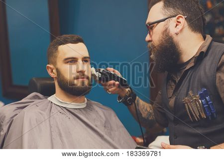 Barber styling beard with trimmer at barbershop. Stylish hairdresser in male hair salon