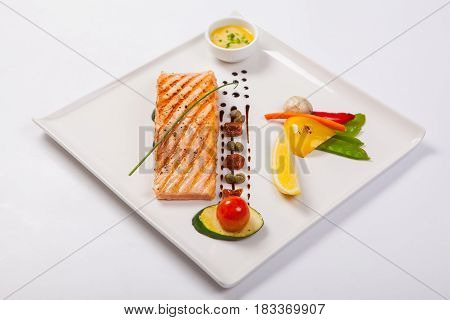 Grilled Salmon And Vegetables On The White Plate