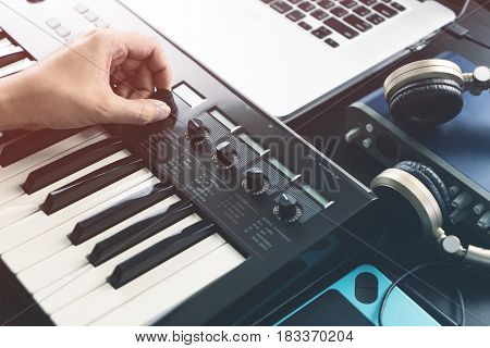 Musician is adjusting sound on synthesizer keyboard