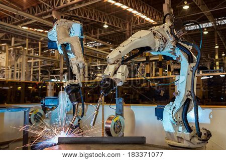 Robot is welding in automotive industrial factory.