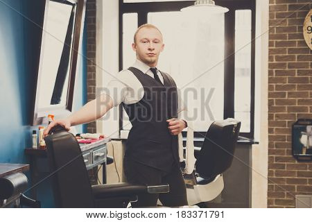 Young elegant barber waits for client, looking at camera. Male hairstylist in barbershop