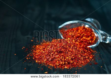 Ground chilli pepper scattered on a dark wooden table. Spice chili on a dark background. Dried chile Pieces. Spice in a glass vase.