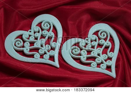 two beautiful openwork carved white hearts on a red background