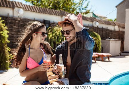 Young beautiful couple smiling, speaking, drinking cocktails, sitting near swimming pool. Copy space.