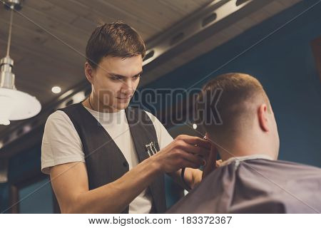 Barber make haircut with hair clipper in barbershop. Stylish hairdresser in male hair salon
