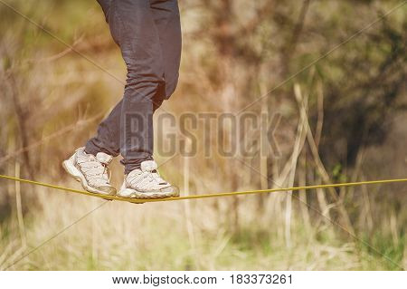 Close-up Slacklining is a practice of balancing, in which nylon or polyester fabric stretched between two anchor points is commonly used. People walk on it and do tricks