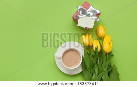 From above a cup of coffee and yellow tulips bunch with small gift with empty note.