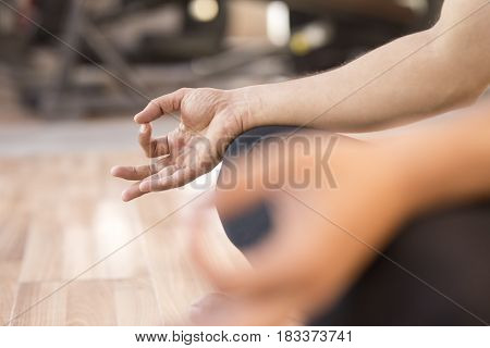 Close-up of man doing yoga meditating on floor