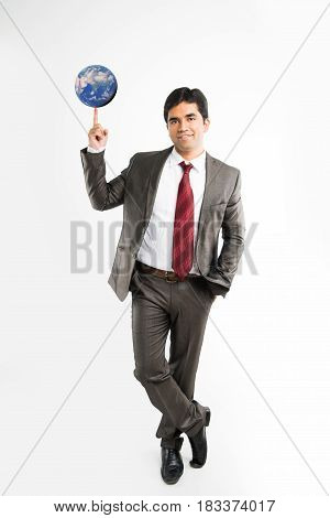 full pic of indian young businessman looking at camera while balancing blue globe or earth model on index finger and wearing complete corporate attire like suit and tie, isolated over white background
