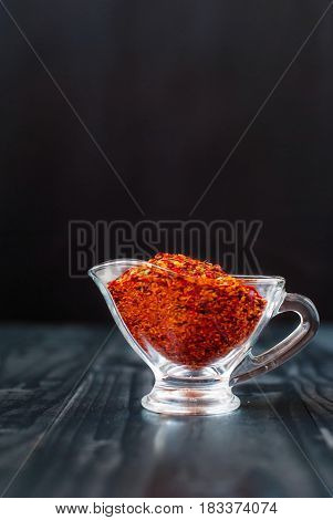 Chili pieces on a dark background. Red pepper dried in a glass jar. Spice on a wooden table. Paprika dried in a glass vase.