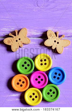 Bright wooden round buttons laid out in the shape of a flower on a green paper sheet, wooden butterfly buttons. Wooden background. Funny summer card. Closeup. Top view. Vertical photo