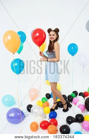 Having party with friends and posing at camera with balloons. Young woman in fancy dress