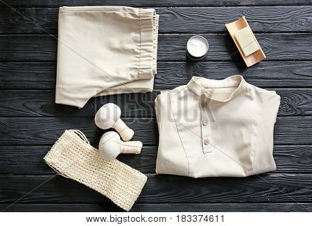 Composition with spa uniform on dark wooden table