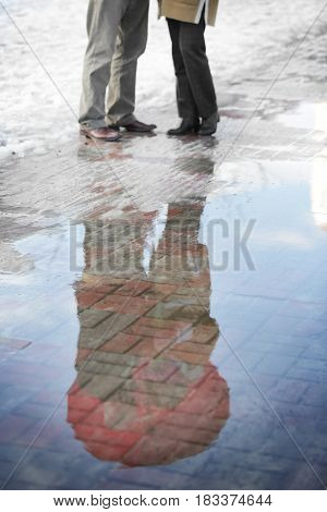 Happy senior couple on a walk, reflection in puddle