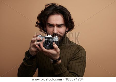 Young handsome man in sweater holding retro photo camera and looking at camera.