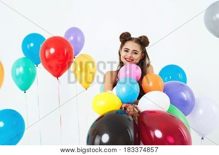 Teen girl in 60s, 70s style clothing posing with colourful balloons at dress code party