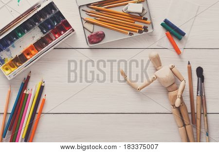 Painting visual art background. Paints and wooden painter man with brushes on white desk, top view, flat lay, objects