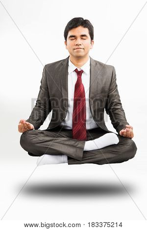 front view or profile view of a flying or floating  indian young businessman meditating in corporate attire in the office or isolated over white background